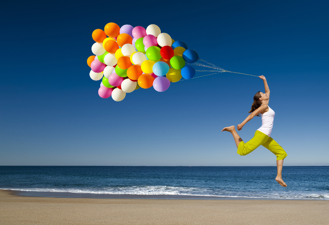 ribose energizes beautiful athletic girl with colorful balloons jumping on the beach